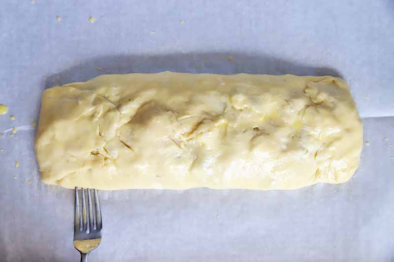 Horizontal image of a fork pressing down on an assembled, unbaked long rectangular pastry on a baking sheet lined with parchment paper.
