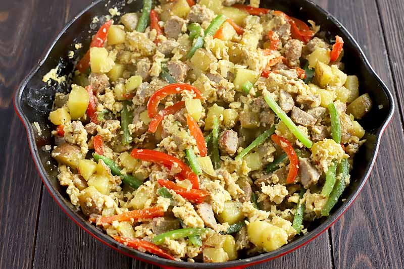 Horizontal image of a skillet with a mixture of eggs, meat, and vegetables.