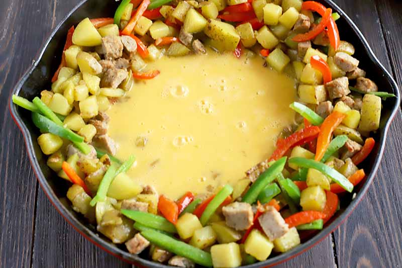Horizontal image of whisked raw egg in the center of a skillet surrounded by mixed vegetables and meat pieces.