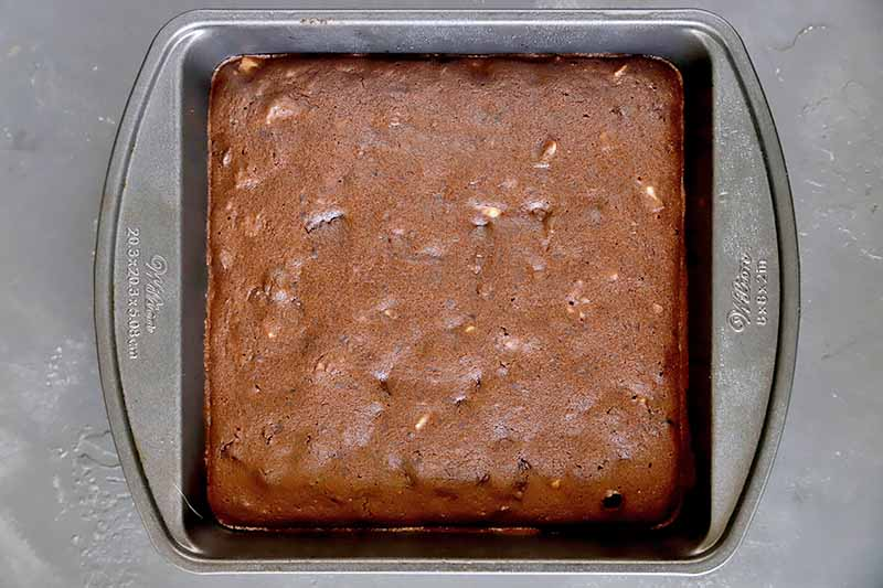 Horizontal image of a square pan with a fluffy baked chocolate dessert.