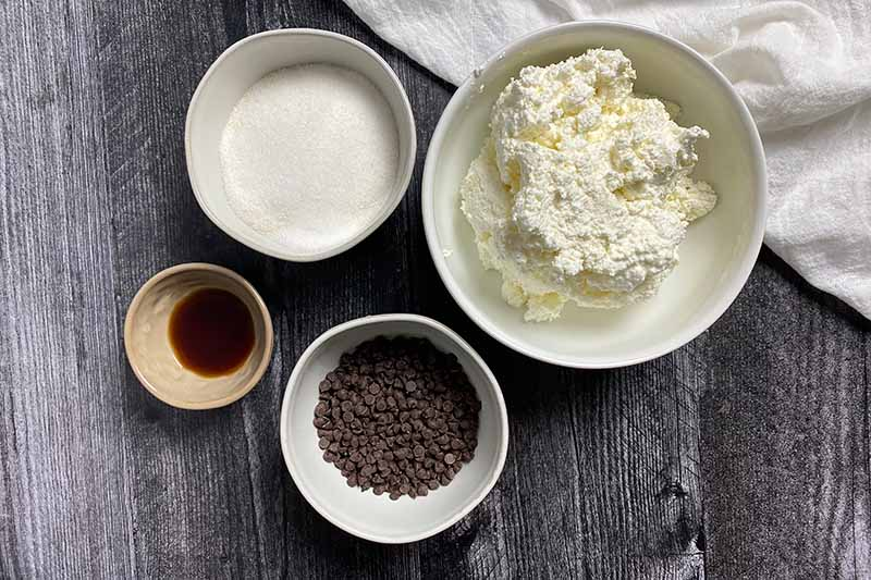 Horizontal image of bowls of fresh cheese, chocolate chips, sugar, and vanilla extract.
