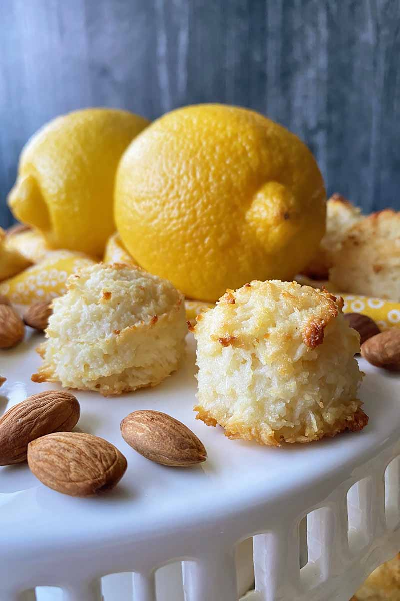 Vertical image of baked coconut mounds and whole nuts on a white platter in front of two whole lemons on a yellow towel.