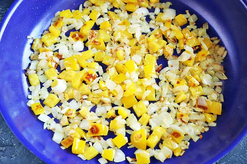 Horiziontal closely cropped overhead image of chopped onion and yellow bell pepper with ground spices in a large blue frying pan.