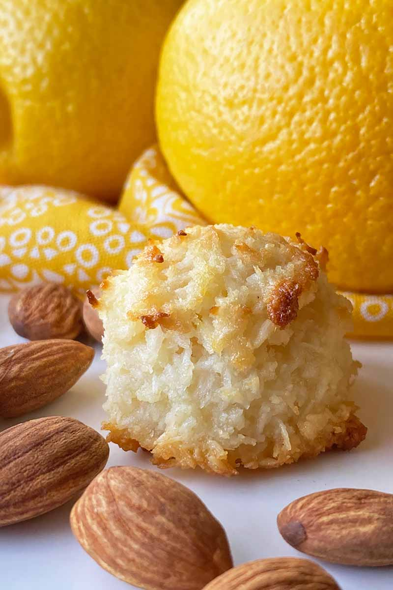 Vertical image of one cookie on a white platter next to whole nuts and in front of a yellow towel and lemons.