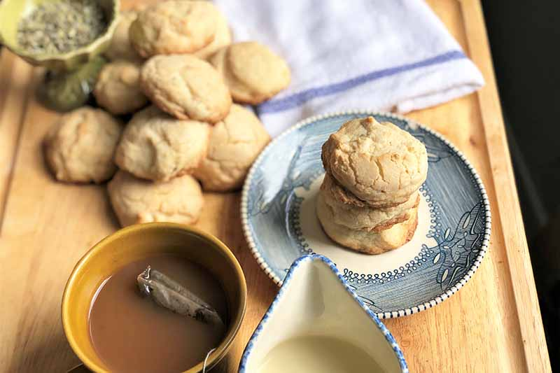 Horizontal image of a towel, cup of tea, cup of cream, a bowl of dried seasonings, and cookies all on a wooden cutting board.