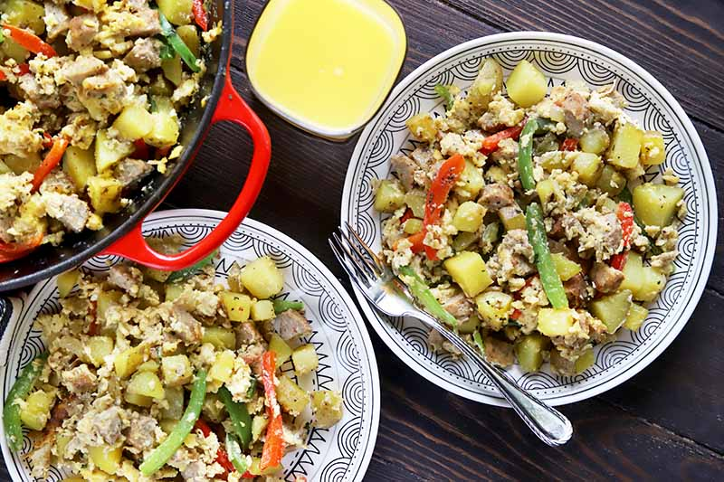 Horizontal top-down image of two plates and a red skillet with a breakfast scramble next to a cup of orange juice.