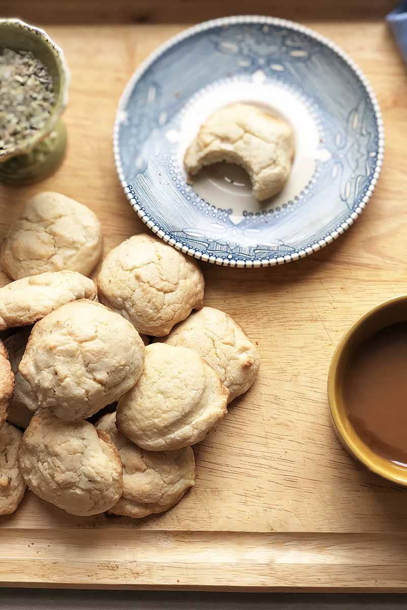 Vertical top-down image of a pile of cookies and a blue plate with another one in the center, all on a wooden cutting board next to a cup of tea and a bowl of dried seasonings.