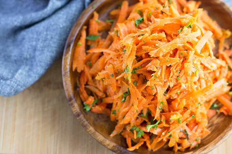Horizontal close-up image of a salad with grated orange vegetables and finely chopped parsley in a wooden bowl next to a blue towel on a wooden table.