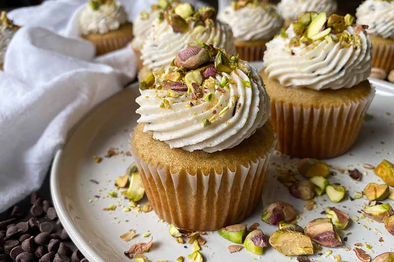 Horizontal image of cupcakes topped with vanilla icing and crushed nuts on a white plate.