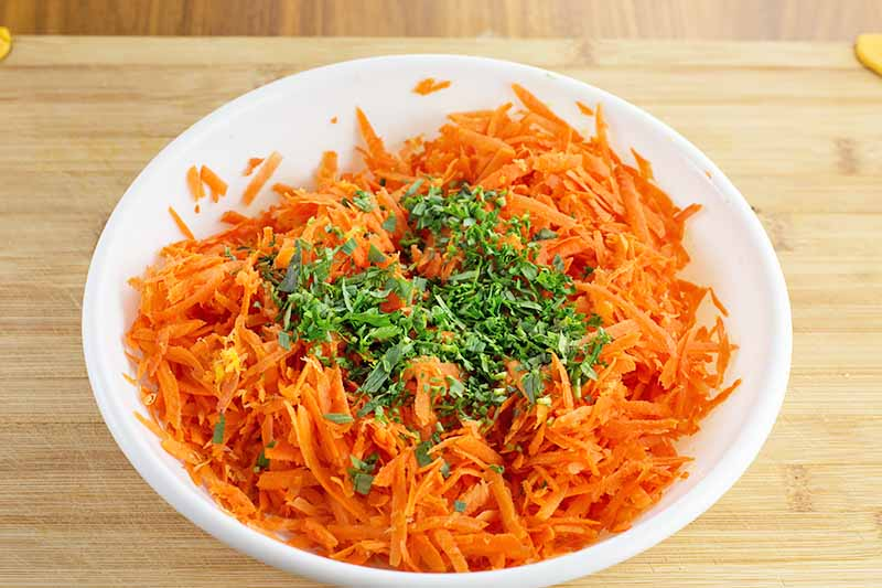 Horizontal image of a white bowl with shredded orange vegetables, lemon zest, and finely chopped green herbs.