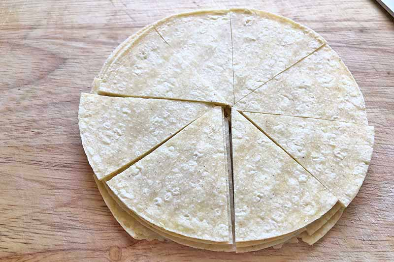 Horizontal image of partially sliced stacked tortillas.