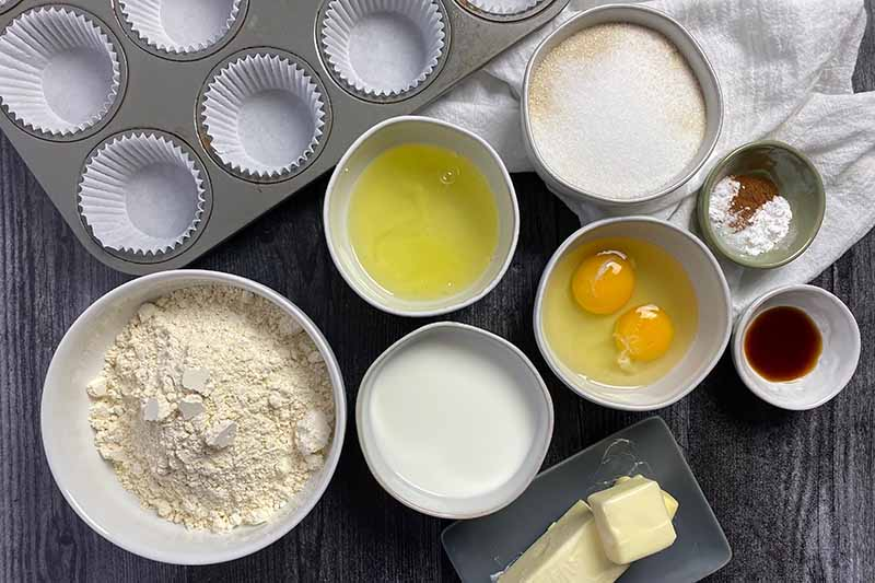 Horizontal image of assorted wet and dry ingredients in white bowls, butter on a gray plate, and a lined muffin pan on a black surface.