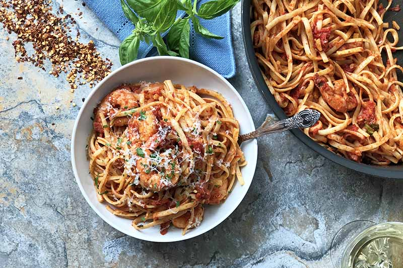 Horizontal image of a white bowl and a large pan filled with linguine and shrimp in a spicy tomato sauce next to red pepper flakes, a blue napkin, basil, and a glass of white wine.