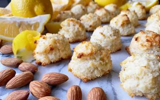 Horizontal image of rows of coconut desserts on a marble platter with whole nuts and lemons.