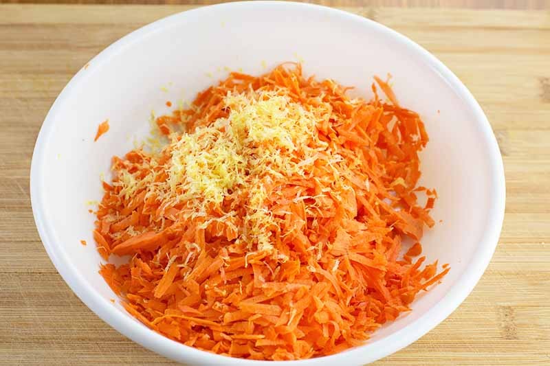 Horizontal image of grated orange vegetables and a heap of lemon zest in a white bowl.