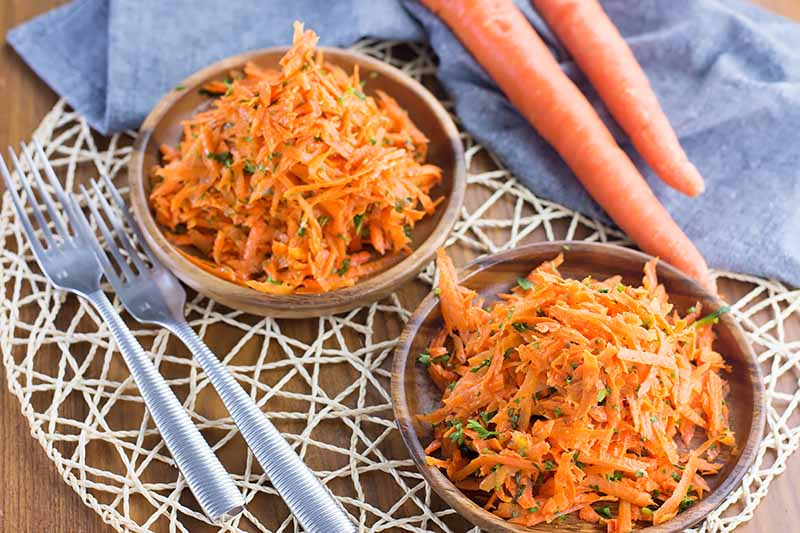 Horizontal image of two wooden bowls full of shredded orange vegetables mixed with fresh herbs on a roped placemat next to a blue towel, whole vegetables, and silverware.