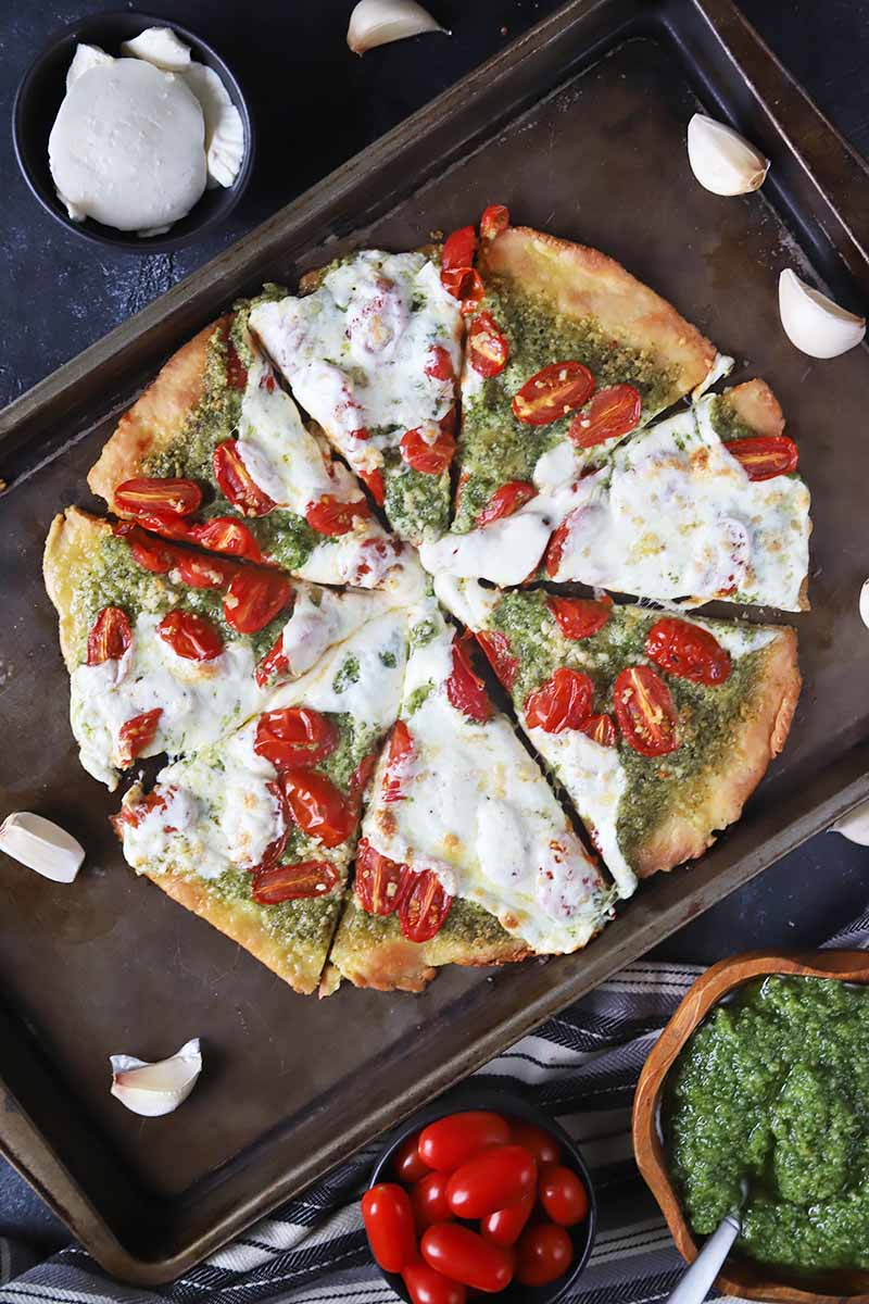 Vertical top-down image of a sliced whole pizza topped with a green sauce, tomatoes, and white cheese on a baking sheet next to whole garlic cloves.