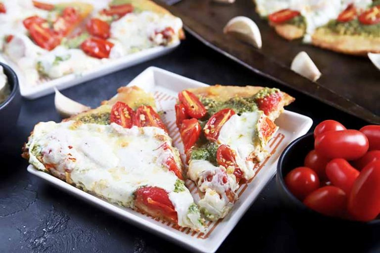 Horizontal image of white square plates topped with pizza slices with green sauce, grape tomatoes, and melted whited cheese on a dark blue surface.