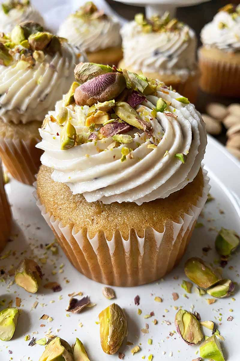 Vertical close-up image of vanilla spice cupcakes decorated with white frosting and crushed nuts on a white plate.