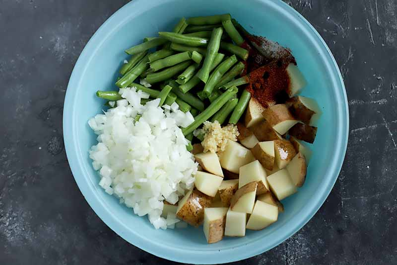 Horizontal image of a blue bowl with chopped beans, onions, potatoes, and seasonings.