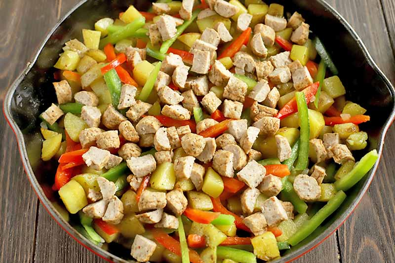 Horizontal image of a skillet with sausage and mixed vegetables.