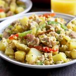 Horizontal image of a plate filled with a mixture of scrambled eggs, sausage, potatoes, and peppers.