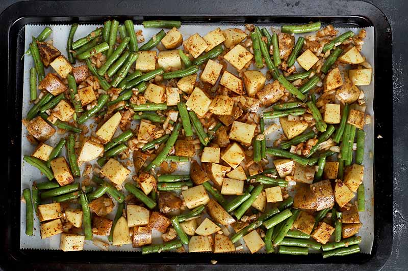 Horizontal top-down image of a tray with roasted assorted vegetables with seasonings.
