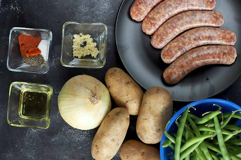 Horizontal image of whole potatoes, green beans, and onions next to a plate of uncooked meat links and glass dishes of various seasonings.