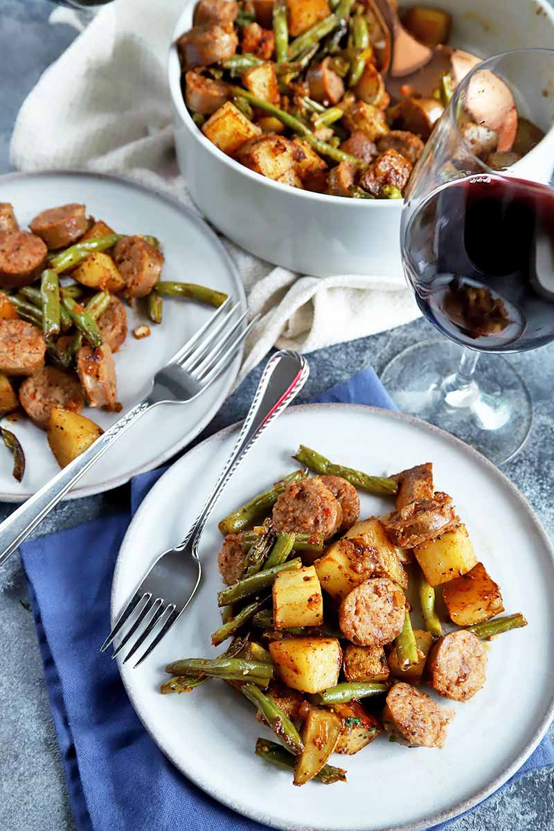 Vertical image of two white plates and a bowl with a meat link and vegetable dinner next to metal forks and a glass of red wine on white and blue napkins.
