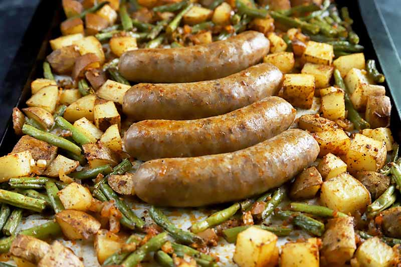 Horizontal image of four whole meat links in the middle of a tray with seasoned potatoes and beans.