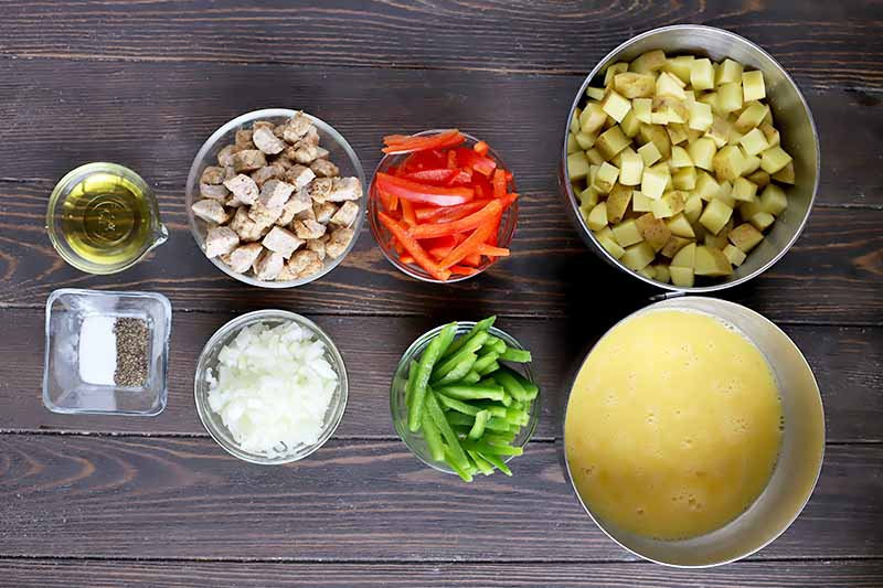 Horizontal image of sliced peppers, chopped onions, potatoes, sausage, oil, seasonings, and whisked eggs in various glass bowls on a dark wooden surface.
