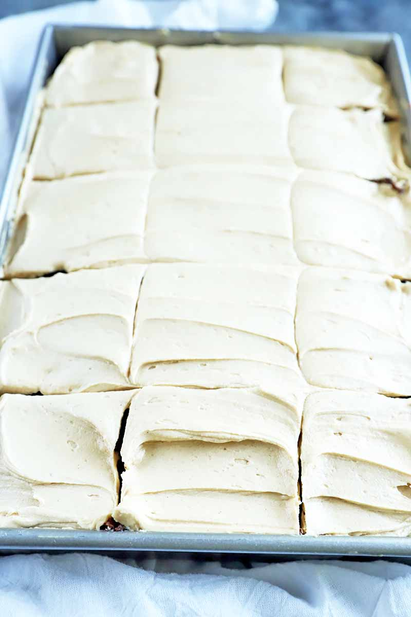 Vertical image of a sheet pan covered in fluffy icing portioned in squares.