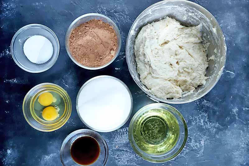 Horizontal image of various bowls with assorted ingredients: eggs, oil, sugar, sourdough starter, cocoa powder, and seasonings.