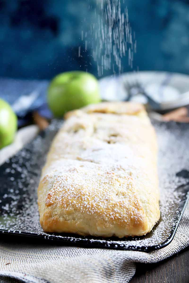 Vertical image of a whole long and skinny pastry being dusted with powdered sugar on a black plate in front of whole green fruit.