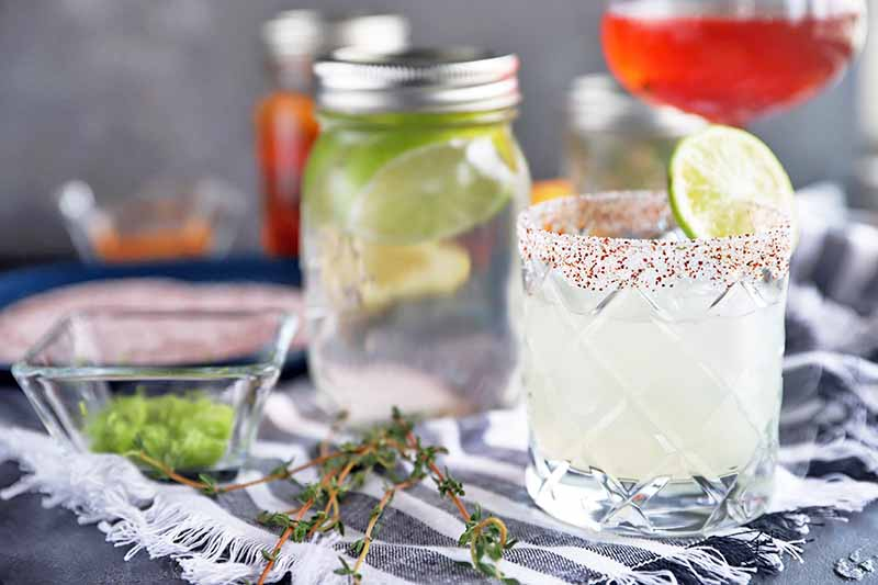 Horizontal image of a cocktail in a lowball glass in the foreground, garnished with a wedge of lime and a spiced salt rim, on a gray surface topped with a gray and white striped cloth with fringe,