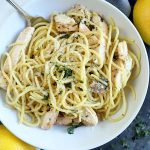 Overhead closely cropped horizontal image of a bowl of spaghetti with chicken, with two lemons on a white and gray cloth, on top of a dark gray surface.