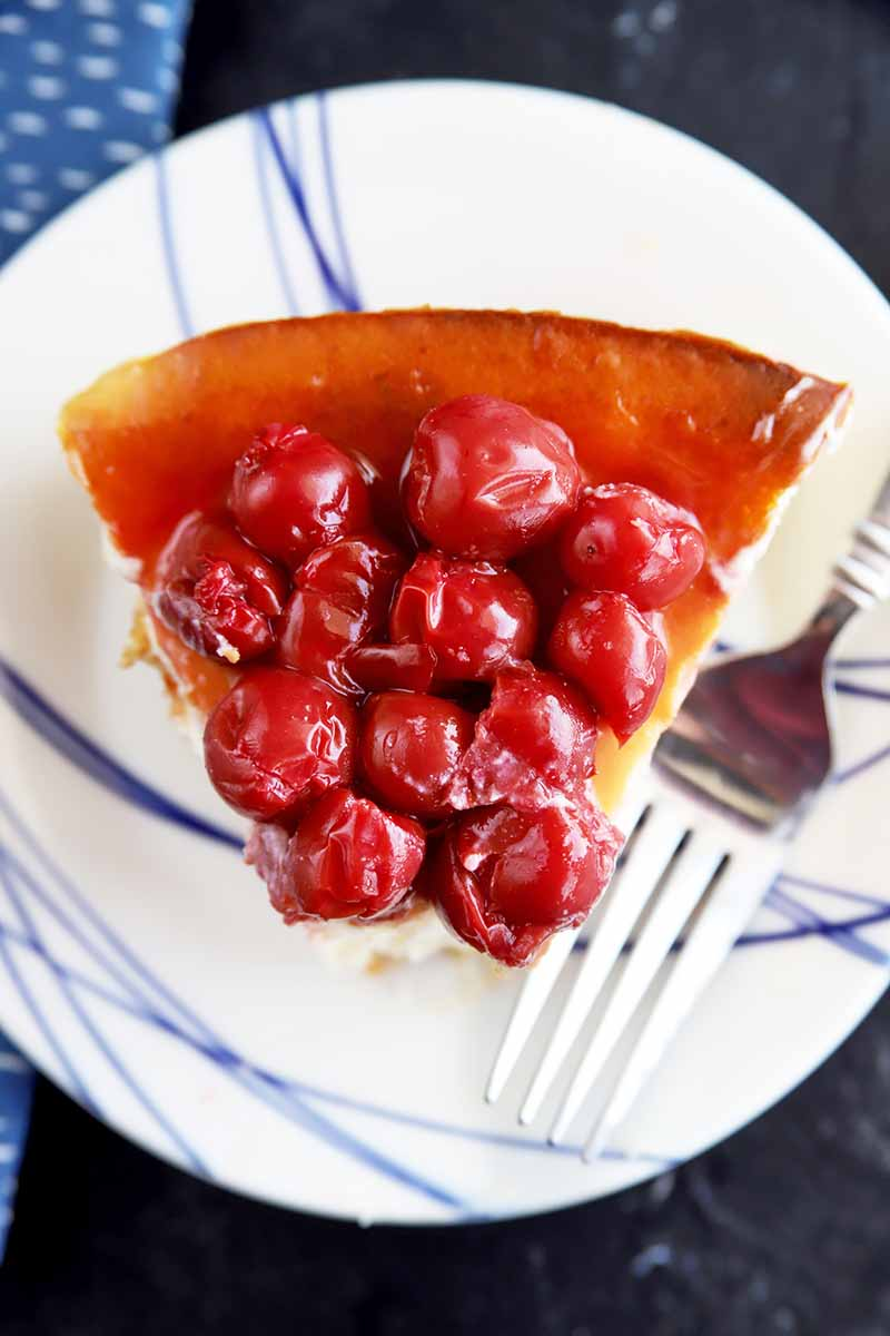Vertical top-down image of a slice of dessert topped with juicy round red fruit on a white plate with blue stripes next to a metal fork.