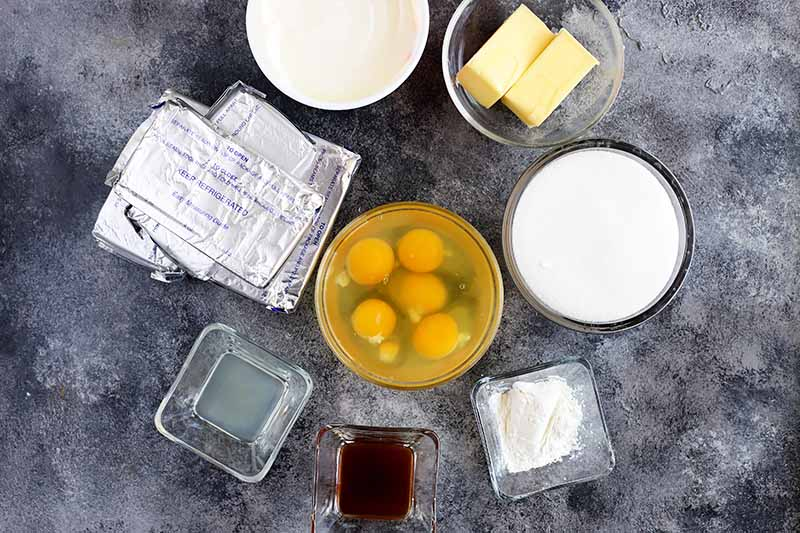 Horizontal image of eggs, butter, creamy ingredients, cream cheese, and other flavorings in dishes on a gray surface.