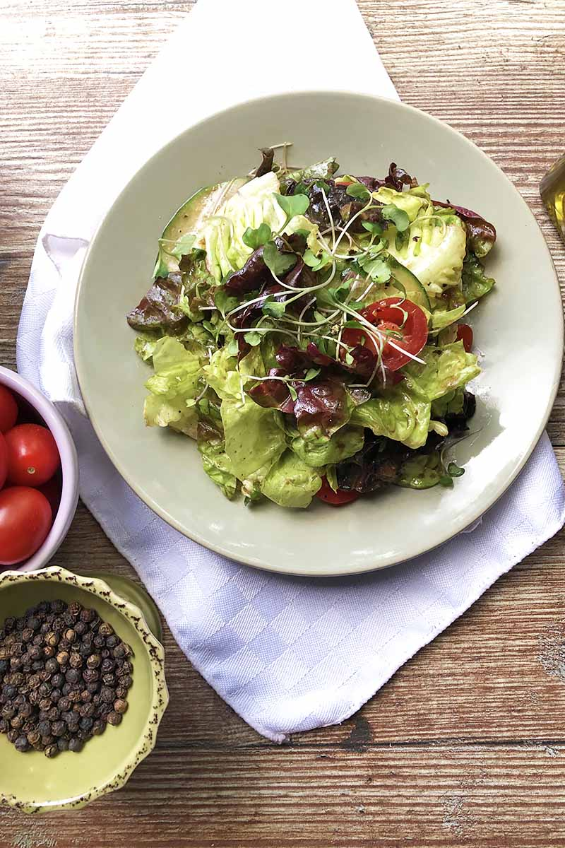Vertical top-down image of a white plate with a butter lettuce, cucumber, and tomato mixture on a white towel next to a bowl of tomatoes, and a bowl of peppercorns.