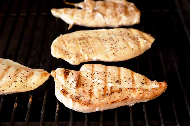 Horizontal image of four chicken breasts cooking on a grill.