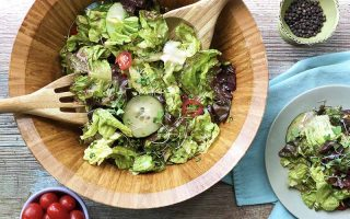 Horizontal image of a white plate on a blue napkin and a wooden bowl with wooden utensils, both full of a colorful mix of vegetables, next to a bowl of tomatoes and a bowl of whole peppercorns.