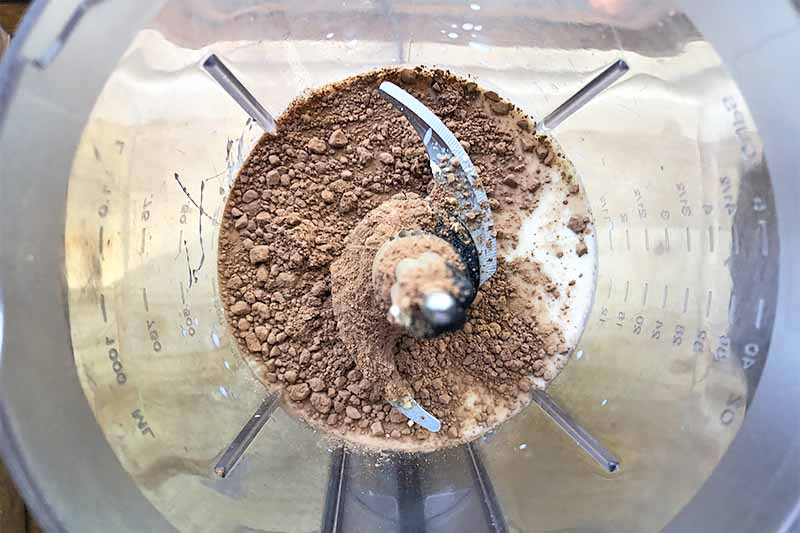 Horizontal image of a blender with cocoa powder and liquids.