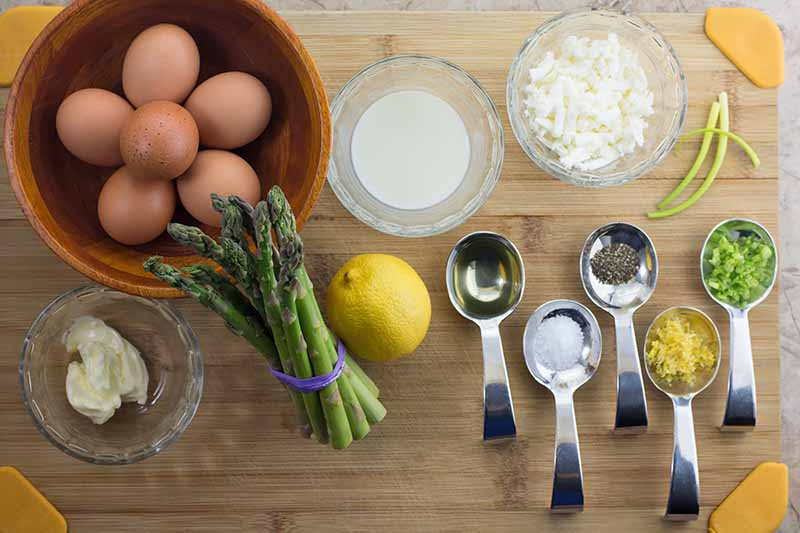 Horizontal image of measured ingredients and whole ingredients to make a vegetable and egg dish.