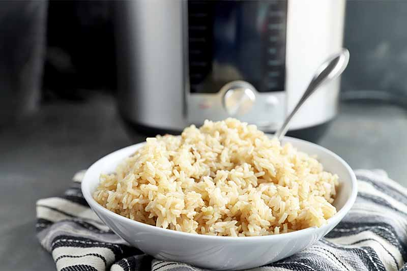 Horizontal image of a white bowl on a white and black towel filled with brown rice with a metal spoon in front of an appliance.