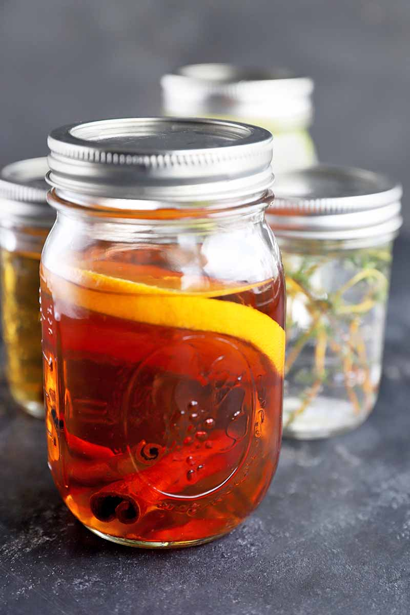 Vertical image of a glass jar with a metal lid on top, filled with bourbon and orange slices, with several more jars filled with flavor-infused liquor in the background in soft focus, on a gray surface against a gray background.