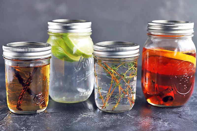 HOrizontal image of four glass jars of various sizes, filled with liquor being infused with vanilla, citrus, or fresh herbs, with metal lids on top, on a gray surface against a gray background.