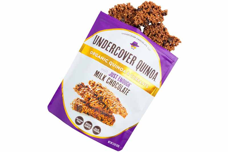 Image of a bag of Undercover Quinoa's milk chocolate-covered quinoa clusters, with some spilling out of the bag.