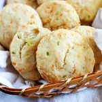 Horizontal image of a basket lined with a white towel filled with cheddar chive biscuits.