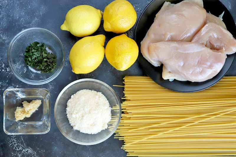 Overhead horizontal image of two round glass bowls of minced herbs and grated parmesan cheese, a small square dish of minced garlic, four lemons, a black plate of boneless, skinless chicken breasts, and a pile of uncooked spaghetti, on a mottled dark gray surface.