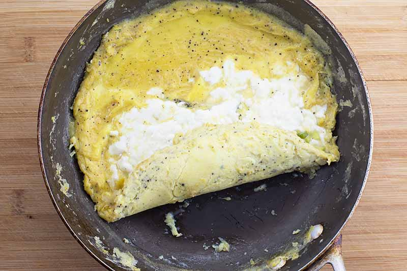 Horizontal image of a partially rolled egg dish with a melted white cheese filling in a skillet.
